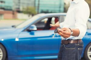 Male hand holding car keys offering new blue car on background.jpeg