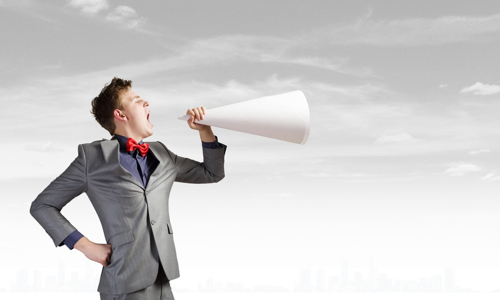 Young businessman screaming emotionally in paper trumpet.jpeg