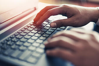 two hands gently placed on top of a keyboard