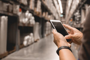 man holding his smartphone in a manufacturing facility