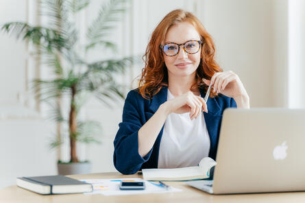 woman in an office smiling from her desk